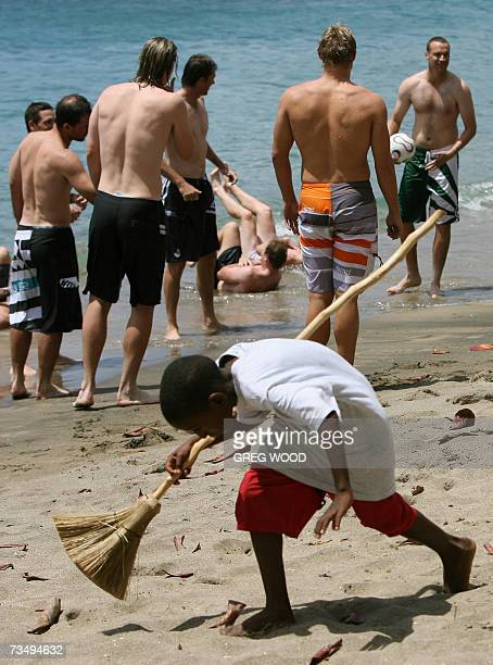 Kingstown, SAINT VINCENT AND THE GRENADINES: A young boy walks across the sand as the Australian World Cup cricket team conduct a recovery session in...