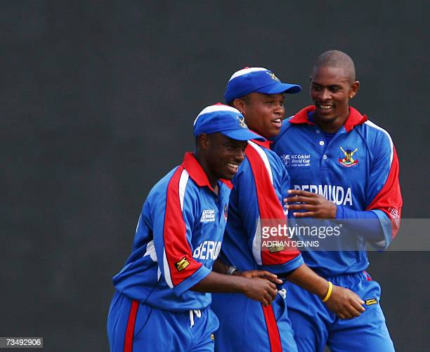Kingstown, SAINT VINCENT AND THE GRENADINES: Bermuda's Kevin Hurdle is congratulated by teammates after taking the wicket of England's Captain...