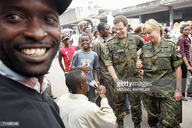 Kinshasa, Democratic Republic of the Congo: Barbara Mueck , captain and ethnologist of the German Bundeswehr shows her EUFOR ensignia to a local 15...