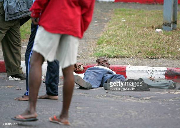 Kinshasa Democratic Republic of the Congo Residents look 21 August 2006 at the body of a man killed during fighting between members of the...