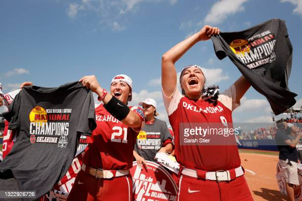 Kinzie Hansen and Grace Green of the Oklahoma Sooners hold up t-shirts after winning Game 3 of the Women's College World Series Championship against...