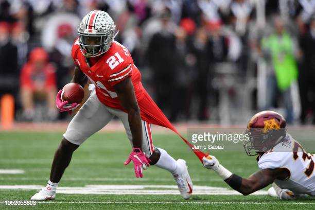 Kiondre Thomas of the Minnesota Golden Gophers keeps a hold on the jersey of Parris Campbell of the Ohio State Buckeyes as Campbell runs upfield in...