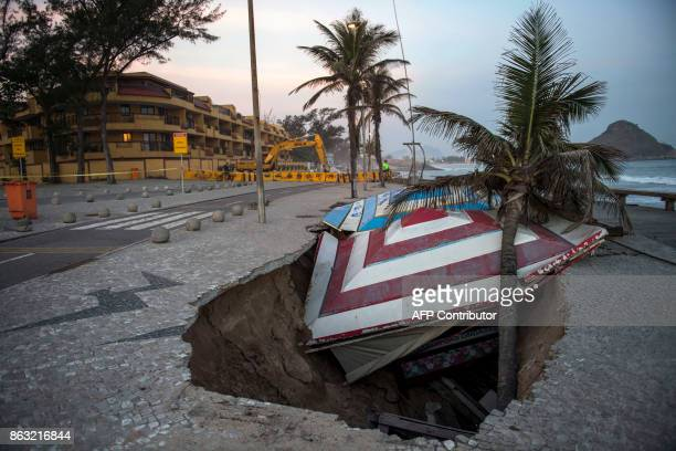 TOPSHOT A kiosk and palm tree collapsed into a sinkhole in a boardwalk destroyed by waves at Macumba beach in Rio de Janeiro Brazil on October 19...