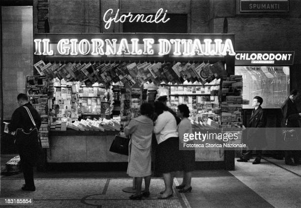 Kiosk for the sale of countless newspapers daily weekly monthly in Rome Italy 1955 Many headers on the market The light sign advertises the head of...