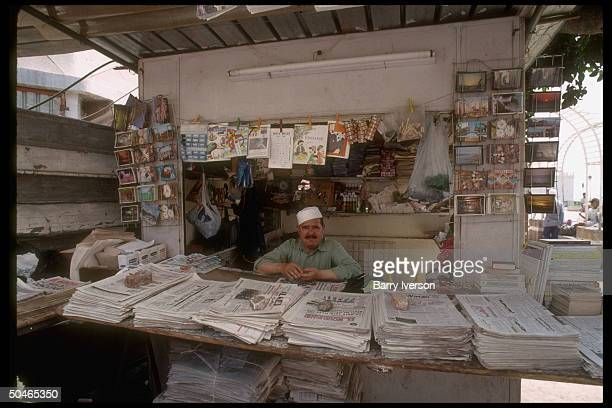 Kiosk offering usual complement of publications postcards sundries w proprietor holding sway behind newspaperpiled counter in casbah area