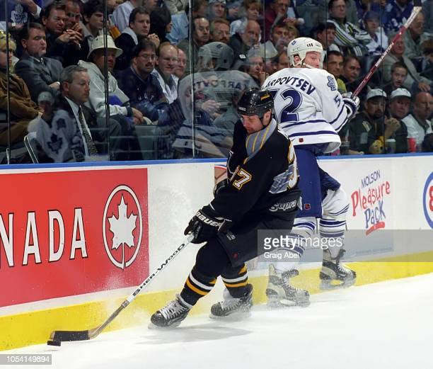 Kip Miller of the Pittsburgh Penguins skates against Alexander Karpovtsev of the Toronto Maple Leafs during the 1999 Quarter Finals of the NHL...