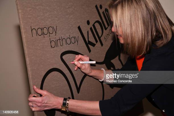Kipling's President Julie Dimperio signs a giant birtday card at Kipling's 25th Anniversary Event at Helen Mills Theater on March 7 2012 in New York...