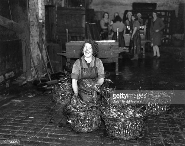 Kipper girl grinning Scotland 24 September 1931 Kipper girl grinning whilst grappling with fish Newhaven Edinburgh Scotland This photograph was taken...