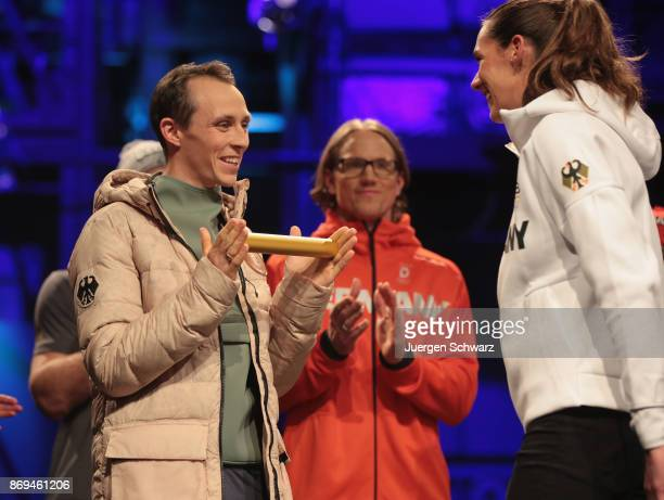 Kira Walkenhorst hands over a baton to Eric Frenzel during the presentation of the outfit for German athletes competing in the upcoming Olympic Games...