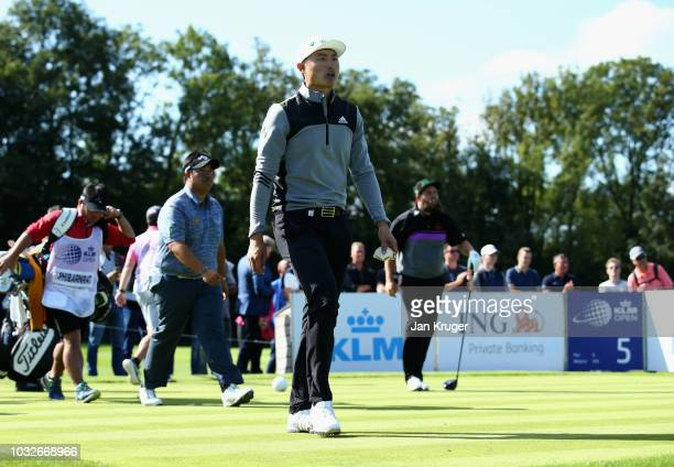 Kiradech Aphibarnrat of Thailand Haotong Li of China and Andrew Johnston of England walk off the 5th tee during day one of the KLM Open at The Dutch...