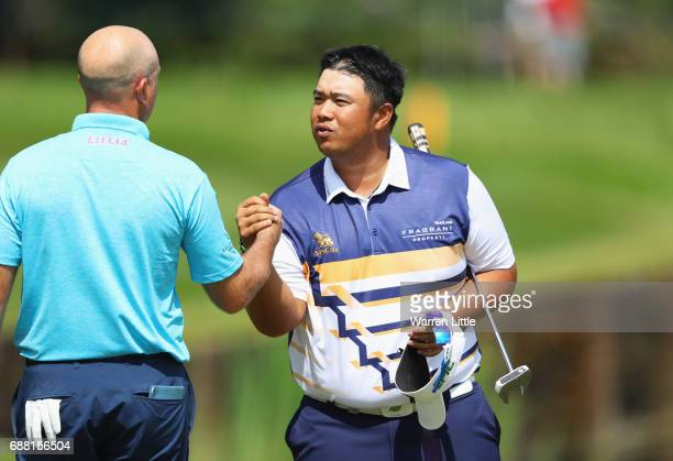 Kiradech Aphibarnrat of Thailand shakes hands with Graeme Storm of England on the 18th green during day one of the BMW PGA Championship at Wentworth...