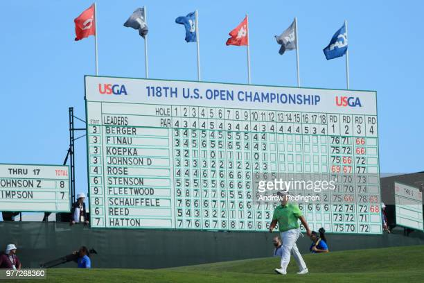 Kiradech Aphibarnrat of Thailand walks in front of a leaderboard on the 14th green during the final round of the 2018 US Open at Shinnecock Hills...