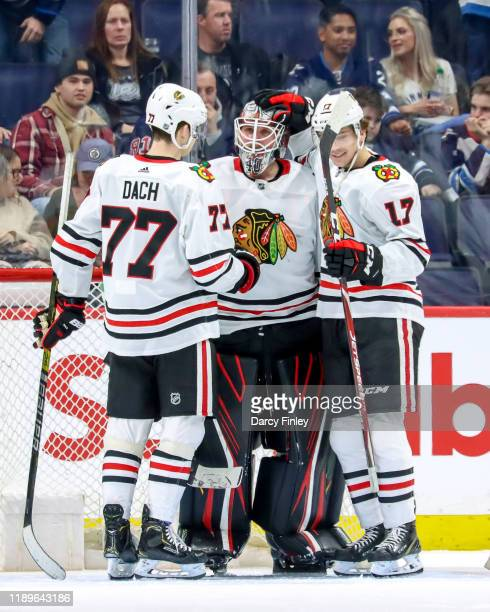 Kirby Dach and Dylan Strome of the Chicago Blackhawks congratulate goaltender Robin Lehner following a 41 victory over the Winnipeg Jets at the Bell...