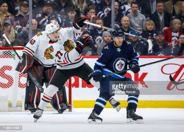 Kirby Dach of the Chicago Blackhawks and Gabriel Bourque of the Winnipeg Jets keep their eyes on the play during first period action at the Bell MTS...