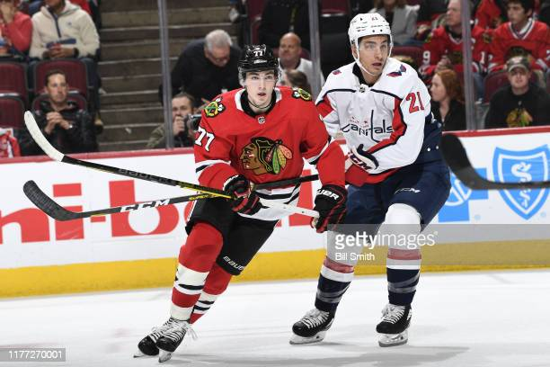 Kirby Dach of the Chicago Blackhawks and Garnet Hathaway of the Washington Capitals watch for the puck in the first period at the United Center on...