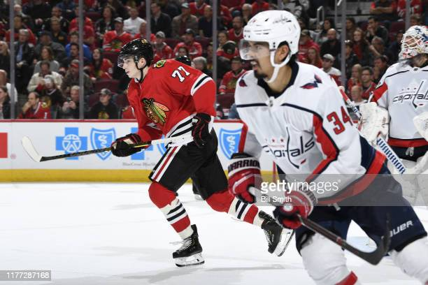 Kirby Dach of the Chicago Blackhawks and Jonas Siegenthaler of the Washington Capitals skate up the ice in the third period at the United Center on...