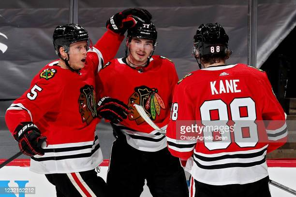 Kirby Dach of the Chicago Blackhawks celebrates with Connor Murphy and Patrick Kane of the Chicago Blackhawks after scoring a goal in the first...