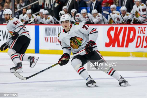 Kirby Dach of the Chicago Blackhawks keeps an eye on the play during first period action against the Winnipeg Jets at the Bell MTS Place on December...