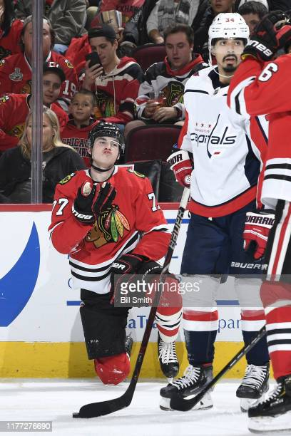 Kirby Dach of the Chicago Blackhawks kneels on the ice after taking a hit from the Washington Capitals in the second period at the United Center on...