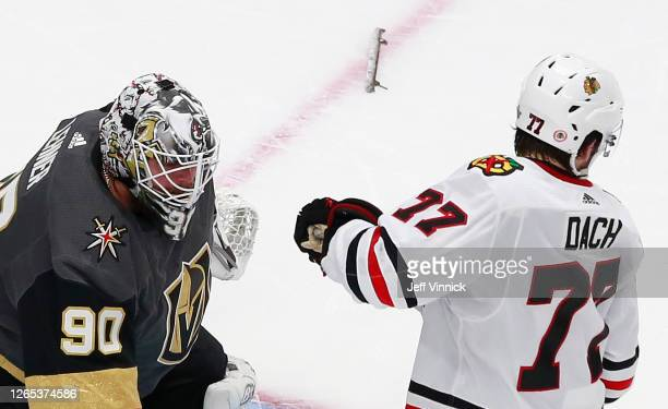 Kirby Dach of the Chicago Blackhawks moves his head back as the broken skate blade from Robin Lehner of the Vegas Golden Knights lays on the ice...
