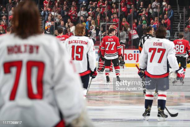 Kirby Dach of the Chicago Blackhawks stands with the starting lineup during the game against the Washington Capitals at the United Center on October...