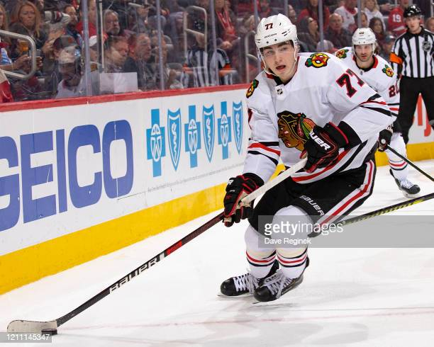 Kirby Dach of the Chicago Blackhawks turns up ice with the puck against the Detroit Red Wings during an NHL game at Little Caesars Arena on March 6,...