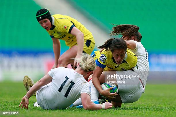Kirby Sefo of Australia is tackled by Marlie Packer of England during the day one of IRB Women's Sevens World Series match between Australia and...