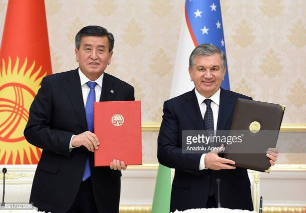 Kirghizstani President Sooronbay Jeenbekov and Uzbekistani President Shavkat Mirziyoyev pose for a photo after signing an agreement during their...
