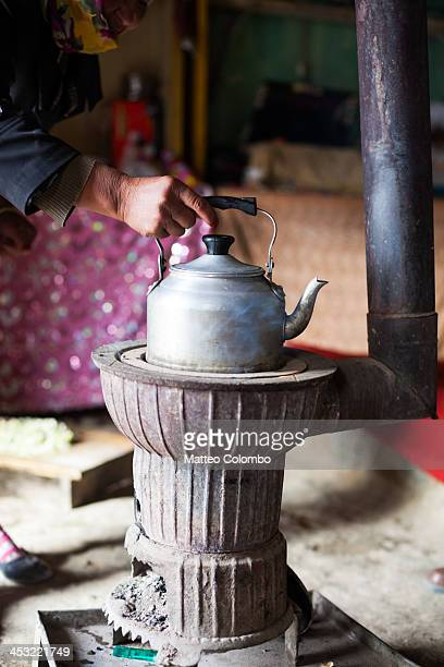 Kirgiz woman preparing tea in a pot inside a yurt