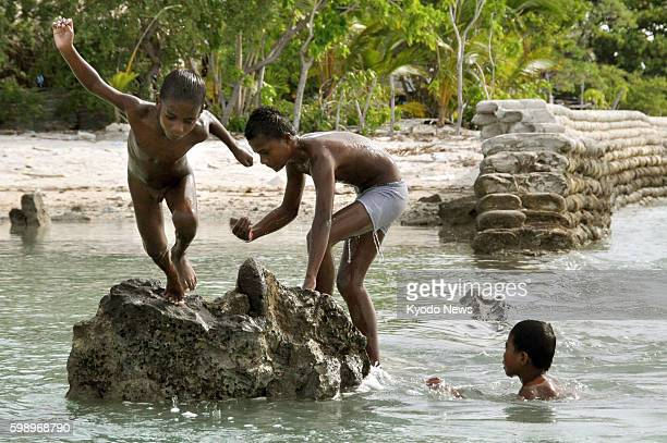 TARAWA Kiribati Children play among the ruins of a levee destroyed by rough waves in Tarawa Kiribati in May 2012 The South Pacific island nation is...
