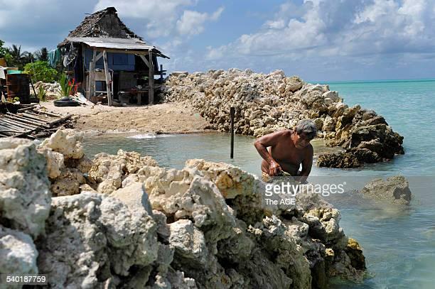 Kiribati Islands Climate Change Albert Ientau 60yrs rebuilding his sea wall to protect his home in the village of Abarao on the island of Tarawa 13...