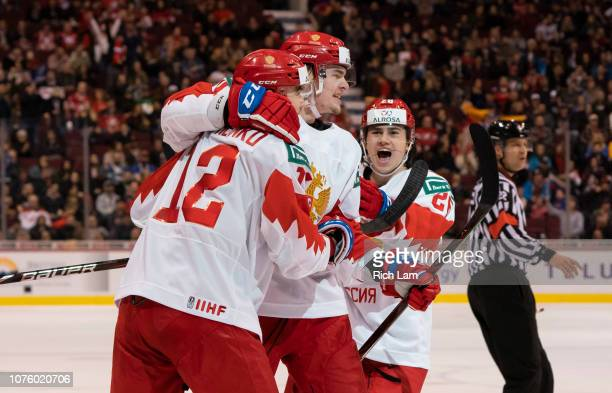 Kirill Marchenko of Russia celebrates with teammates Alexander Alexeyev and Alexander Romanov after scoring a goal in Group A hockey action of the...