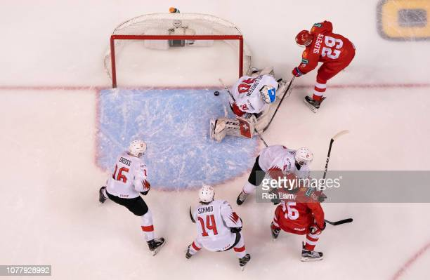 Kirill Slepets of Russia slides the puck past goalie Luca Hollenstein of Switzerland in Bronze Medal hockey action of the 2019 IIHF World Junior...