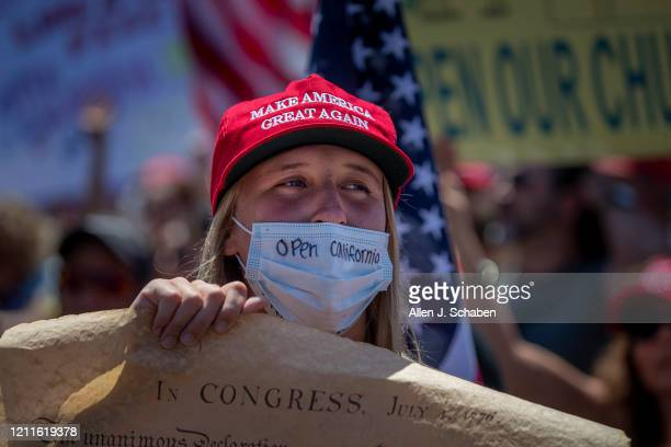 Kirk A protester sporting a message on her protective mask and holding the U.S. Constitution poster, sends a message to Gov. Newsom while joining...