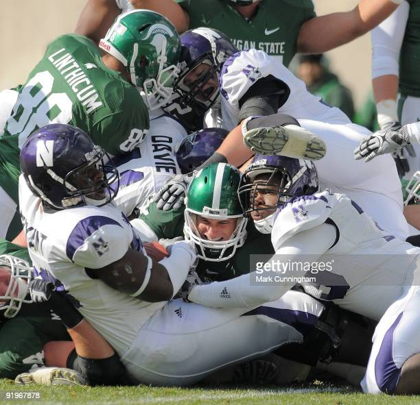 Kirk Cousins of the Michigan State Spartans is tackled short of the goal line on a 4th down play in the first quarter by the Northwestern Wildcats...