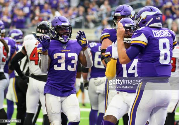Kirk Cousins of the Minnesota Vikings celebrates with teammates after scoring a touchdown in the second quarter of the game against the Atlanta...