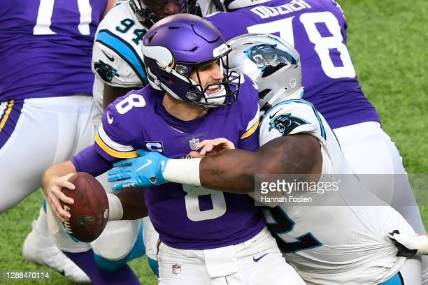 Kirk Cousins of the Minnesota Vikings fumbles the ball as he is sacked by Zach Kerr of the Carolina Panthers during the third quarter at U.S. Bank...