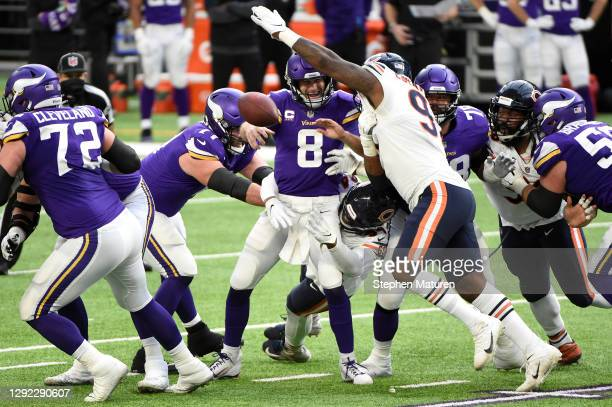 Kirk Cousins of the Minnesota Vikings gets rid of the ball as he is pressured by Mario Edwards Jr. #97 of the Chicago Bears during the first half at...