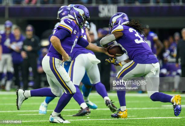 Kirk Cousins of the Minnesota Vikings hands the ball off to Dalvin Cook of the Minnesota Vikings in the first quarter of the game against the Detroit...