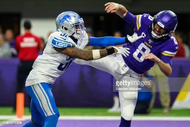 Kirk Cousins of the Minnesota Vikings is hit by Tavon Wilson of the Detroit Lions after throwing the ball in the fourth quarter of the game at US...
