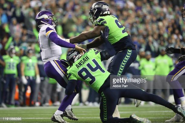 Kirk Cousins of the Minnesota Vikings is hit by Ziggy Ansah and Jarran Reed of the Seattle Seahawks in the fourth quarter during their game at...