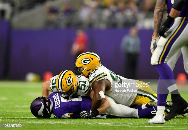 Kirk Cousins of the Minnesota Vikings is sacked by Kyler Fackrell and Kenny Clark of the Green Bay Packers in the third quarter of the game at US...