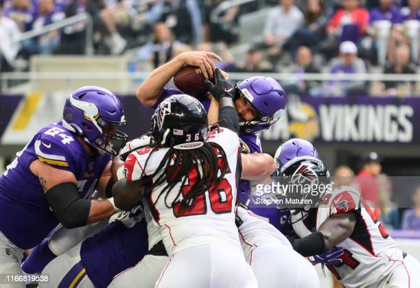 Kirk Cousins of the Minnesota Vikings leaps with the ball for a touchdown in the second quarter of the game against the Atlanta Falcons at U.S. Bank...