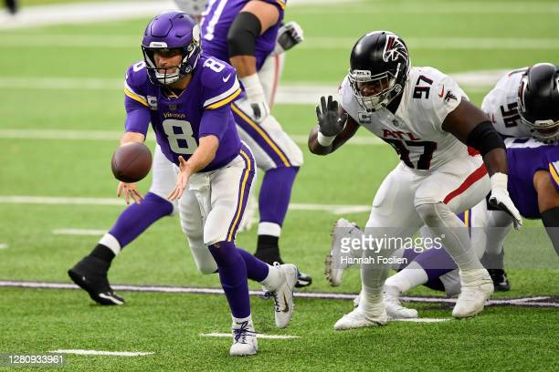 Kirk Cousins of the Minnesota Vikings pitches the ball while being chased by Grady Jarrett of the Atlanta Falcons in the first quarter at U.S. Bank...