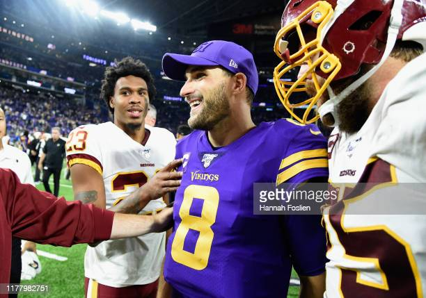 Kirk Cousins of the Minnesota Vikings speaks with Quinton Dunbar and Brandon Scherff of the Washington Redskins after the game at US Bank Stadium on...