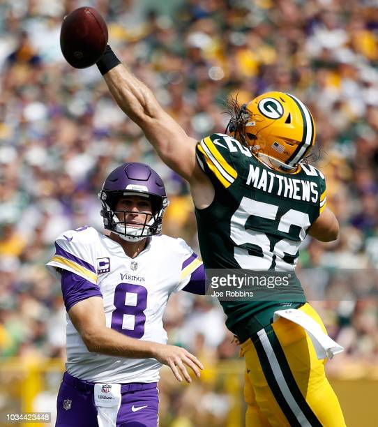 Kirk Cousins of the Minnesota Vikings throws a ball past Clay Matthews of the Green Bay Packers during the first quarter of a game at Lambeau Field...