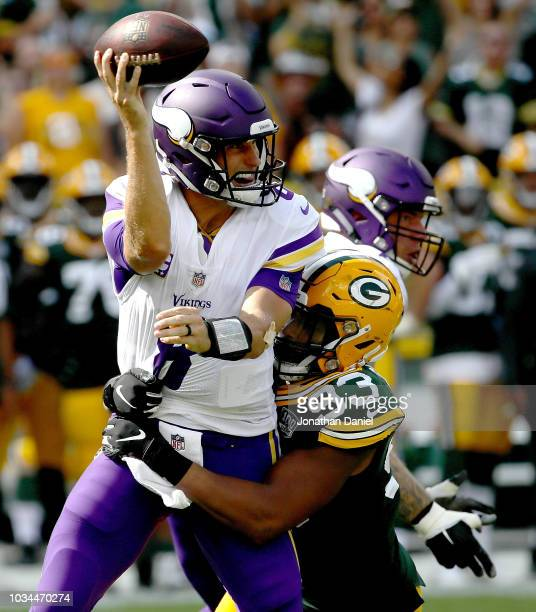 Kirk Cousins of the Minnesota Vikings throws the ball away while being chased by Reggie Gilbert of the Green Bay Packers during the third quarter of...