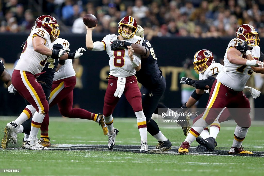 Kirk Cousins #8 of the Washington Redskins is hit as he throws by David Onyemata during the first half at the Mercedes-Benz Superdome on November 19, 2017 in New Orleans, Louisiana.