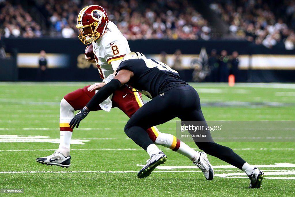 Kirk Cousins #8 of the Washington Redskins is tackled by Vonn Bell #48 of the New Orleans Saints during the first half at the Mercedes-Benz Superdome on November 19, 2017 in New Orleans, Louisiana.