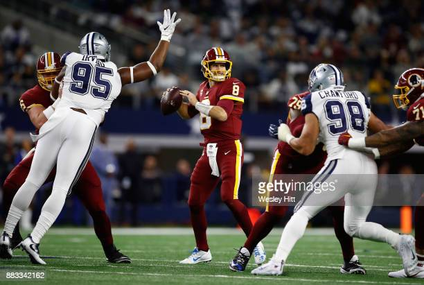 Kirk Cousins of the Washington Redskins looks to pass in in the first quarter of a football game as David Irving and Tyrone Crawford of the Dallas...